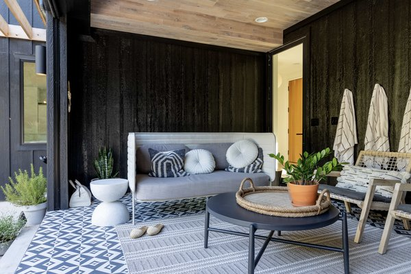 One of Kevin's favorite rooms is an indoor-outdoor area he calls the 'screen room.' With a full-width retractable screen across one wall, the space is a modern take on an all-season screened porch.