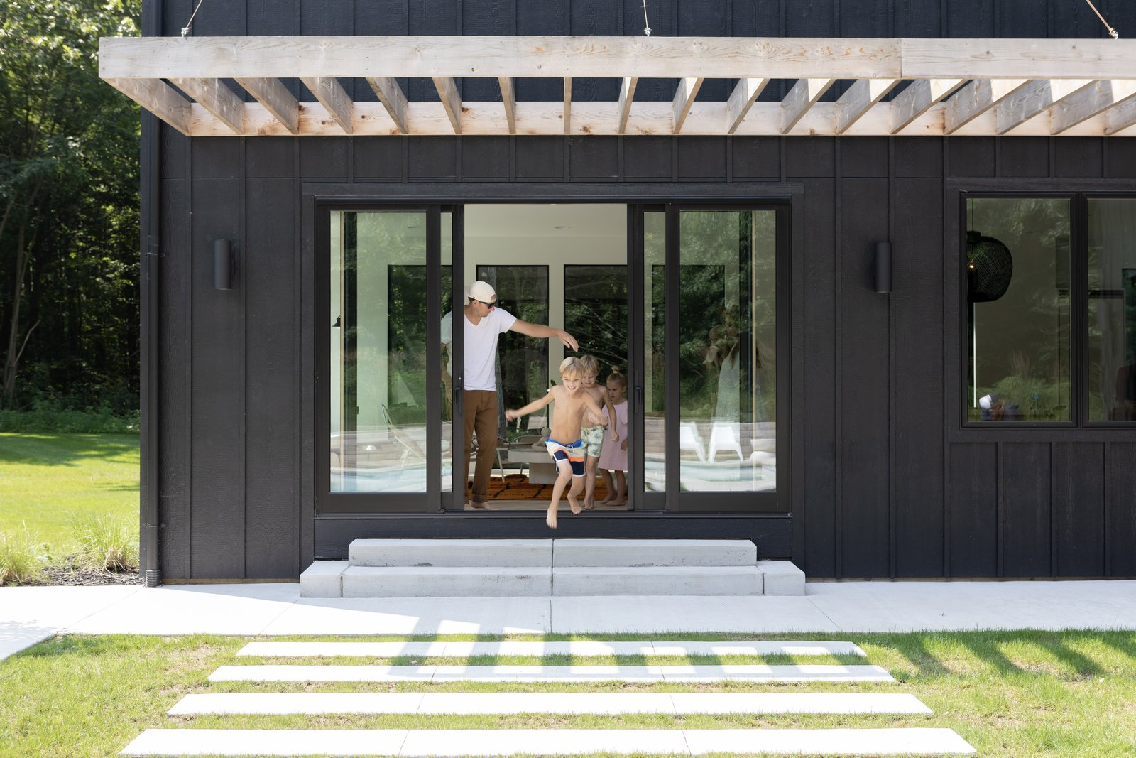 Doors, Exterior, and Sliding Door Type Large slider doors from Marvin allow easy access to the patio. The couple chose  long rectangular stepping blocks in the exact width of the slider to further enhance the view outward.  Photo 9 of 10 in Watch How This Danish-Style Farmhouse Unites a Family With Nature