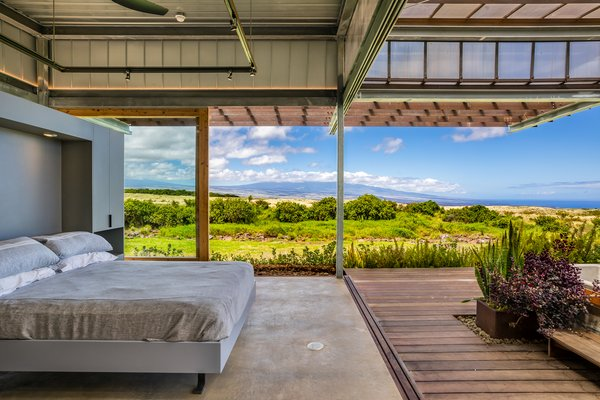 At one corner of the expansive space, near the living room, a more intimate bedroom space is created by a simple wardrobe structure. The room is open on two sides, framing 180-degree views of the landscape and creating a connection with the outdoors just steps from the bed.