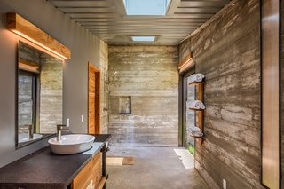 Inside the bunkers, each one serves a different purpose, with some used as storage and others used as private living ares. Here, this bathroom features simple finishes of local wood, with skylights overhead to brighten the space.