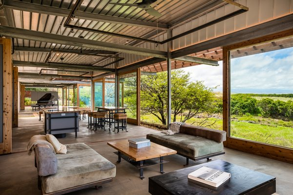 A look at the main living area, which opens to the kitchen and looks out onto sweeping views of the Pacific Ocean and vast lava escarpments. This entire section of the home retains an indoor-outdoor ambiance created by the large glass doors that open up the front wall.