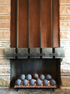 The fireplace holds a modern gas insert. Hall originally built the five-foot-wide fireplace to recirculate heat using inset iron pipes and convection to project warm air throughout the room.