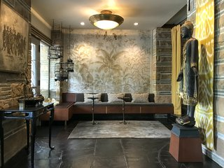Today, the entrance features a restored version of the original bench and new hand-painted wallpaper. The original slate floors were tinted black to hide years of abuse and lack of maintenance.