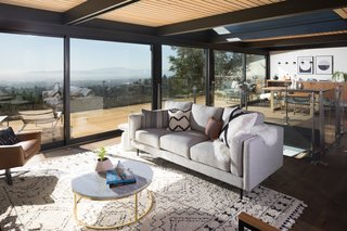 Flanking each side of a central window in the living and dining space are two massive Series 600 Sliding Glass Doors from Western Window Systems. Such large doors create a strong indoor-outdoor connection for entertaining and enjoying the bay breeze.