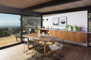 Countertops and cabinets form a buffet area in the dining room, extending seamlessly from the kitchen. As in the living room, a matching Series 600 Sliding Glass Door opens to the deck.