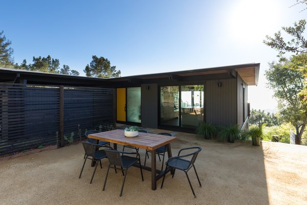 A courtyard along the side yard provides additional entertaining space off the kitchen. Large sliding doors and windows from Western Window Systems provide a sightline out the glazed rear of the home.