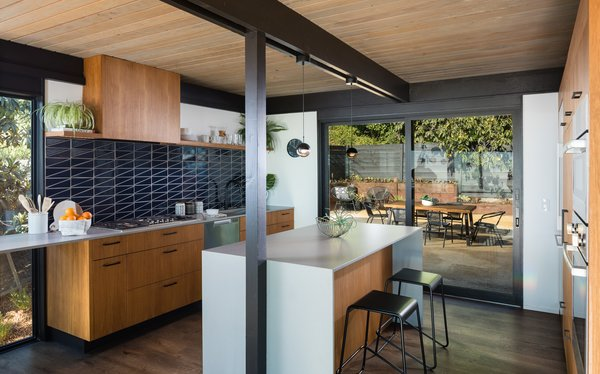 An open kitchen was rebuilt to face the rear courtyard. Contemporary features include a pop of color contrasting with teak veneer cabinetry and other wood tones.
