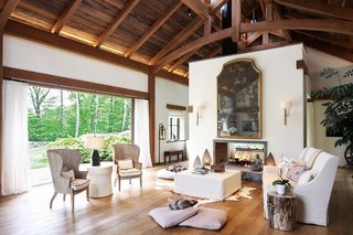 Inside the guest house, exposed beams along the rafters create a barn-like atmosphere, which is enhanced by a double-sided fireplace. Large sliding doors provide natural air circulation and enhance the indoor-outdoor connection.