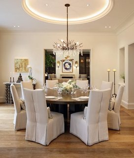 A formal dining room is located between the kitchen and living room. The space features a crystal-decorated antler chandelier underneath a circular raised ceiling.