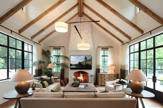 The Country French style is more apparent in the family room, which features a cathedral ceiling strapped with wooden beams. Natural light seeps into the space from large windows and doors along both sides of the room, as well as dormer windows along the ceiling.
