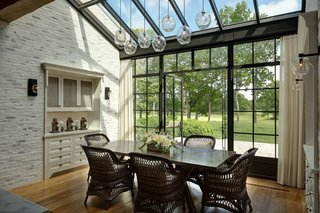 A breakfast nook off the kitchen is designed as a solarium and looks out onto the lush backyard. The glass ceiling and wall of windows allow sunshine to warm the space, which also features an exposed brick wall and built-in china cabinets on both sides.