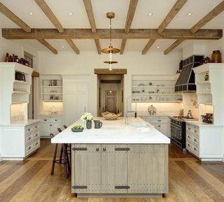 In the kitchen, a huge central island is complete with marble countertops and cabinetry in a rustic-looking finish. Hutch-like cabinets sit along each of the opposite sides, while built-in appliances and shelving line the back wall.