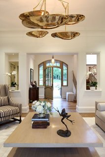 A view of the entry way and formal living room. The space features a neutral color palette and warm hardwood flooring.