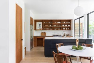 The sleek kitchen opens to dining area. A wood island is painted black to visually contrast against Himalayan marble countertops and lighter wood tones.