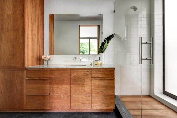 The master bathroom continues many themes found throughout the rest of the home. Dense ipe wood, which clads the exterior and porch columns, was also chosen to line the shower floor, while lightly oiled cherry makes up the bathroom cabinetry.