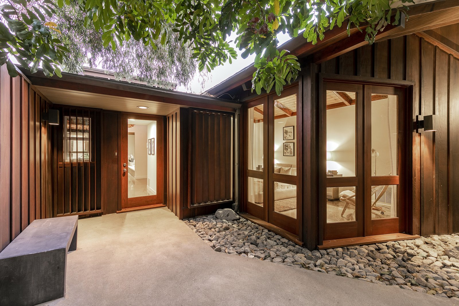 A view of the main entrance, which appears nestled within the trees. The minimalist exterior is clad in wood and surrounded by stones, creating a Zen-like retreat.