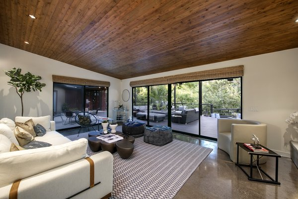 The large living area offers a striking wood-clad ceiling. Large sliding doors wrap around the room, providing access to the deck and framing views of the treetops.