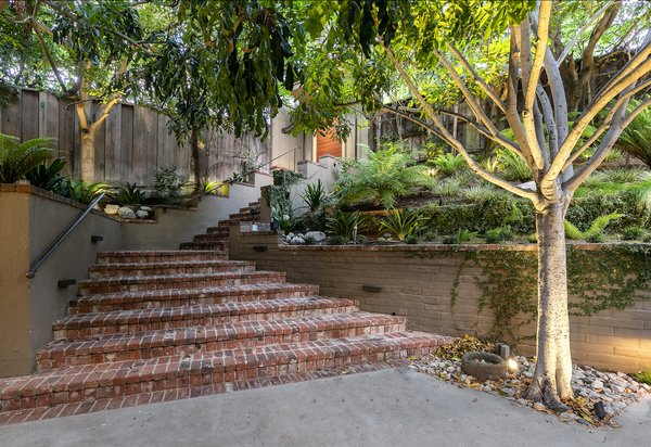 From a gate along the street, brick stairs lead down to a sunken courtyard and the home's main entrance. A separate gated driveway provides access to a two-car garage.