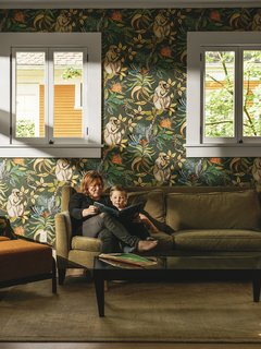 The formerly somber space got a splash of color and whimsy with monkey-themed Savuti  wallpaper by Cole & Son. The sofa is from Lazar and the Gilda chair is by Porada.