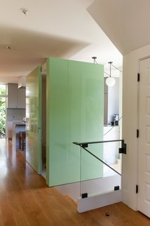 The home's main entryway, with stairs leading down to a basement. A small powder room is tucked away in a seafoam-green boxed wall, with the kitchen hidden from view behind it.