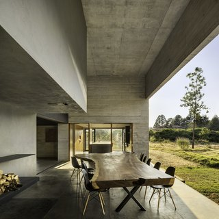 Eames chairs surround the live-edge dining table on a terrace.