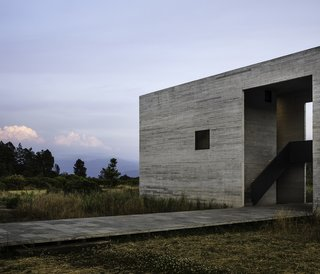 "Architects Javier Sánchez and Carlos Mar of JSa created a bold house in Valle de Bravo that emerges from the setting in three parts like ""excavated stone boxes."" Valle de Bravo that emerges from the setting in three parts like ""excavated stone boxes. Inspired by Donald Judd's minimalist works, the three volumes feature board-formed concrete walls accented with charred wood. Strategically placed cutouts and windows frame views within and between the volumes and out to the surrounding terrain."