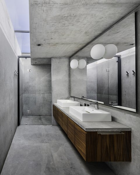 The concrete master bathroom is illuminated by a skylight.