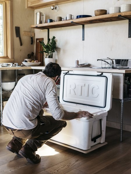 Below the sink, a cooler slides out on a plywood board with the help of casters. The whole kitchen was built for $1,000.