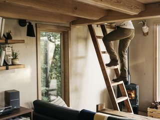 Jeff climbs the hand-built ladder to the sleeping loft. Both the ladder and bench in front of the sofa were made from fallen Pacific madrone trees on the property.