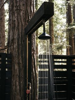 Molly and Jeff wanted their guests to have creature comforts, so early on they built an outdoor shower that's illuminated by string lights at night.