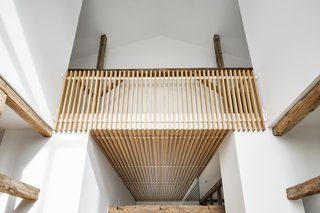 Looking from the dining area, wood cladding extends from the entryway ceiling up to railings in a second floor loft.