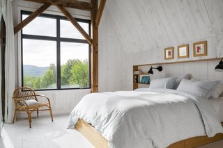 An oversize window in a bedroom offers views of the Sutton Mountains.