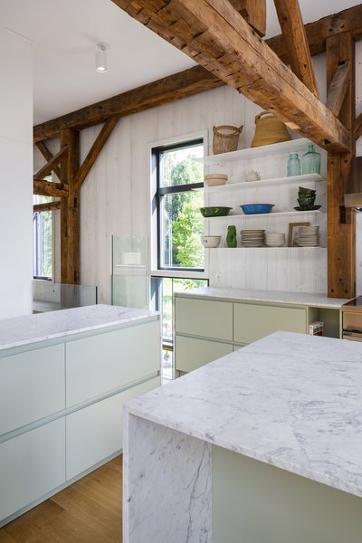 The interior utilizes mixes of wood, glass, and stone for a clean, modern look. Refrigerator drawers are concealed in the island to help keep sightlines open throughout the space.