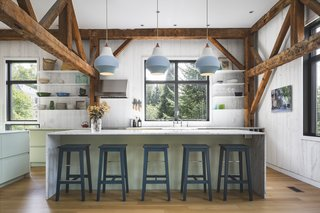 The open kitchen features timber-beamed ceilings and marble countertops. Around the island, Louis Poulsen pendants complement IKEA stools painted Hague Blue by Farrow & Ball. The range hood is by Sub-Zero.