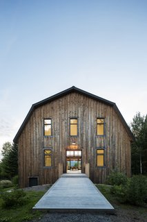 A wood bridge leads to the second-floor entry of the converted barn, which now offers 4,500-square feet of clean, modern interior space. The cladding is local hemlock spruce, the same local wood that was originally used to build the barn.