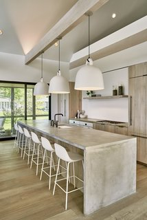 """The kitchen is one of Lindsay's favorite spaces in the house. There, she can be part of the action going on inside while enjoying sweeping views of the outside. The concrete island by <span style=""""font-family: Theinhardt, -apple-system, BlinkMacSystemFont, &quot;Segoe UI&quot;, Roboto, Oxygen-Sans, Ubuntu, Cantarell, &quot;Helvetica Neue&quot;, sans-serif;"""">Bomanite of Wisconsin</span><span style=""""font-family: Theinhardt, -apple-system, BlinkMacSystemFont, &quot;Segoe UI&quot;, Roboto, Oxygen-Sans, Ubuntu, Cantarell, &quot;Helvetica Neue&quot;, sans-serif;""""> and reclaimed oak cabinetry are brightened with white Bell pendants by Normann Copenhagen and Fiber stools by Muuto. The </span><span style=""""font-family: Theinhardt, -apple-system, BlinkMacSystemFont, &quot;Segoe UI&quot;, Roboto, Oxygen-Sans, Ubuntu, Cantarell, &quot;Helvetica Neue&quot;, sans-serif;"""">cabinet pulls are by Berenson, the </span><span style=""""font-family: Theinhardt, -apple-system, BlinkMacSystemFont, &quot;Segoe UI&quot;, Roboto, Oxygen-Sans, Ubuntu, Cantarell, &quot;Helvetica Neue&quot;, sans-serif;"""">cooktop and fridge by Miele</span><span style=""""font-family: Theinhardt, -apple-system, BlinkMacSystemFont, &quot;Segoe UI&quot;, Roboto, Oxygen-Sans, Ubuntu, Cantarell, &quot;Helvetica Neue&quot;, sans-serif;"""">he, the </span><span style=""""font-family: Theinhardt, -apple-system, BlinkMacSystemFont, &quot;Segoe UI&quot;, Roboto, Oxygen-Sans, Ubuntu, Cantarell, &quot;Helvetica Neue&quot;, sans-serif;"""">faucet by Kohler, and the </span><span style=""""font-family: Theinhardt, -apple-system, BlinkMacSystemFont, &quot;Segoe UI&quot;, Roboto, Oxygen-Sans, Ubuntu, Cantarell, &quot;Helvetica Neue&quot;, sans-serif;"""">sink by Blanco.</span><span style=""""font-family: Theinhardt, -apple-system, BlinkMacSystemFont, &quot;Segoe UI&quot;, Roboto, Oxygen-Sans, Ubuntu, Cantarell, &quot;Helvetica Neue&quot;, sans-serif;"""">   </span>"""