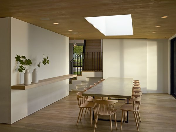 """In the dining room, a custom table surrounded by J104 chairs from Hay can accommodate up to 14 people. <span style=""""font-family: Theinhardt, -apple-system, BlinkMacSystemFont, &quot;Segoe UI&quot;, Roboto, Oxygen-Sans, Ubuntu, Cantarell, &quot;Helvetica Neue&quot;, sans-serif;"""">The wall paint is Snowbound by Sherwin-Williams</span><span style=""""font-family: Theinhardt, -apple-system, BlinkMacSystemFont, &quot;Segoe UI&quot;, Roboto, Oxygen-Sans, Ubuntu, Cantarell, &quot;Helvetica Neue&quot;, sans-serif;"""">.</span>"""