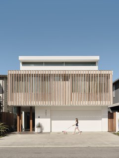A front view of the renovated home. The wood slats screening the bedrooms on the street-facing side are repeated indoors on the interior staircase.