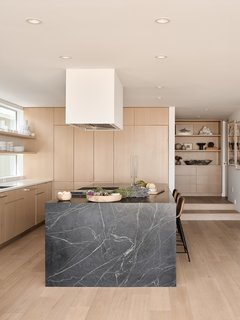 A soapstone island contrasts with white oak cabinetry and flooring in the kitchen. The stools are from Palecek.