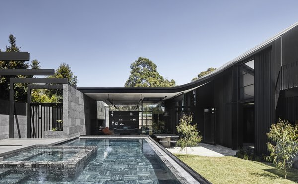 The home's sloping roofline sweeps upward from an enclosed courtyard. The character of the house changes as light hits the mix of materials—from rough stone to sleek black aluminum—throughout the day, giving it a sense of constant motion.