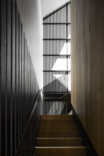 Black timber contrasts with a warm wood tone leading up the stairs.