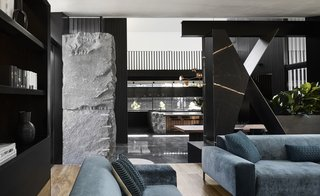 """In the living room, Splinter Society designed a sculptural divider made of African gold marble, mild steel, and smoked mirror. The sofas are from Meizai and the <span style=""""font-family: Theinhardt, -apple-system, BlinkMacSystemFont, &quot;Segoe UI&quot;, Roboto, Oxygen-Sans, Ubuntu, Cantarell, &quot;Helvetica Neue&quot;, sans-serif;"""">throw pillows are from Figgoscope Curates</span><span style=""""font-family: Theinhardt, -apple-system, BlinkMacSystemFont, &quot;Segoe UI&quot;, Roboto, Oxygen-Sans, Ubuntu, Cantarell, &quot;Helvetica Neue&quot;, sans-serif;"""">.</span>"""