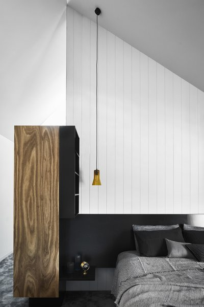 A Silhouette pendant by Ross Gardam hangs in the bedroom. The linens are from Cultiver, and the black throw pillows are from Figgoscope Curates. The alarm clock is by George Nelson for Vitra, and the resin objects by Emma Davies.
