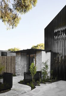 Another view of the monolithic stones that flank each side of the main entrance. Ribbons of black aluminum on the streetside facade appear to seamlessly twist as they reveal windows and offer a peek of greenery.