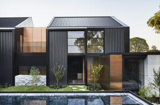 The native plantings in the courtyard, which is enclosed by a wall for privacy in the suburban setting, visually link it to the established eucalyptus trees at the front and rear of the property. The home's dark cladding is accented by rose gold stainless steel panels.