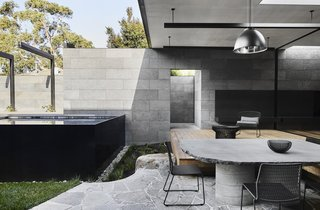 An outdoor patio area sits under a covered area looking out onto the private courtyard.