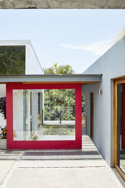 Opening to the home's main entrance on the upper level, a large red sliding door—one of three—is painted Gypsy Red by Sherwin-Williams. To the left is the kitchen and dining space, and to the right is the living room and studio.