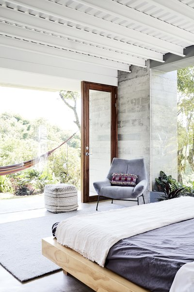 The ceiling is exposed corrugated metal salvaged from the old house's pitched roof and reused as decking for the concrete slab overhead. The space also features a Jessie Velvet armchair from Altea Design, a Dune pouf by Kare Design, and a Quinn wool rug from Crate & Barrel. Outside, a hammock beckons.