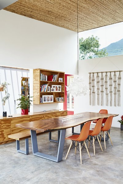 Much of the furniture— including the nine-foot dining table created from a single slab of a fallen Guanacaste tree—was custom made by local millworker HDM. The Eames Molded chairs are from Herman Miller, and the pendant light from IKEA.