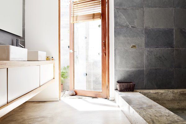 Inside, a sunken concrete tub faces a plywood and fiberboard vanity designed by the couple. The sinks are by Domus and the faucets are by Glacier Bay.